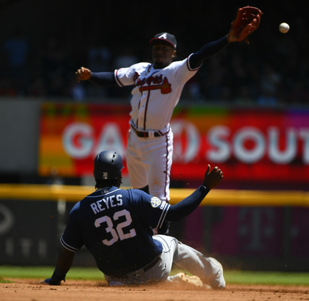 San Diego Padres' Franmil Reyes (32) is safe at second base as Atlanta Braves second baseman Ozzie Albies can't reach a throw from pitcher Mike Foltyn...