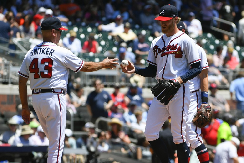 Atlanta Braves pitcher Mike Foltynewicz hands a ball to manager Brian Snitker (43) as he is relieved after allowing multiple scores by the San Diego P...