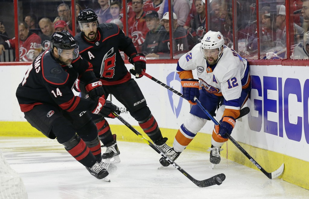 Carolina Hurricanes' Justin Williams (14) takes the puck from New York Islanders' Josh Bailey (12) while Hurricanes' Justin Faulk (27) looks on at rea