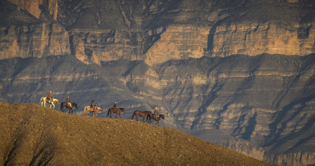 In this December 2017 photo released by Fin and Fur Films, a group of filmmakers and wildlife photographers ride horseback in Big Bend National Park, ...
