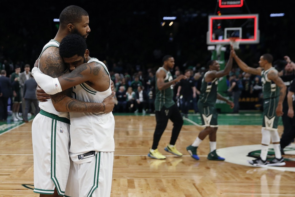 Boston Celtics' Marcus Morris, left, hugs Kyrie Irving as the Milwaukee Bucks celebrate their 123-116 win in Game 3 of a second round NBA basketball p...