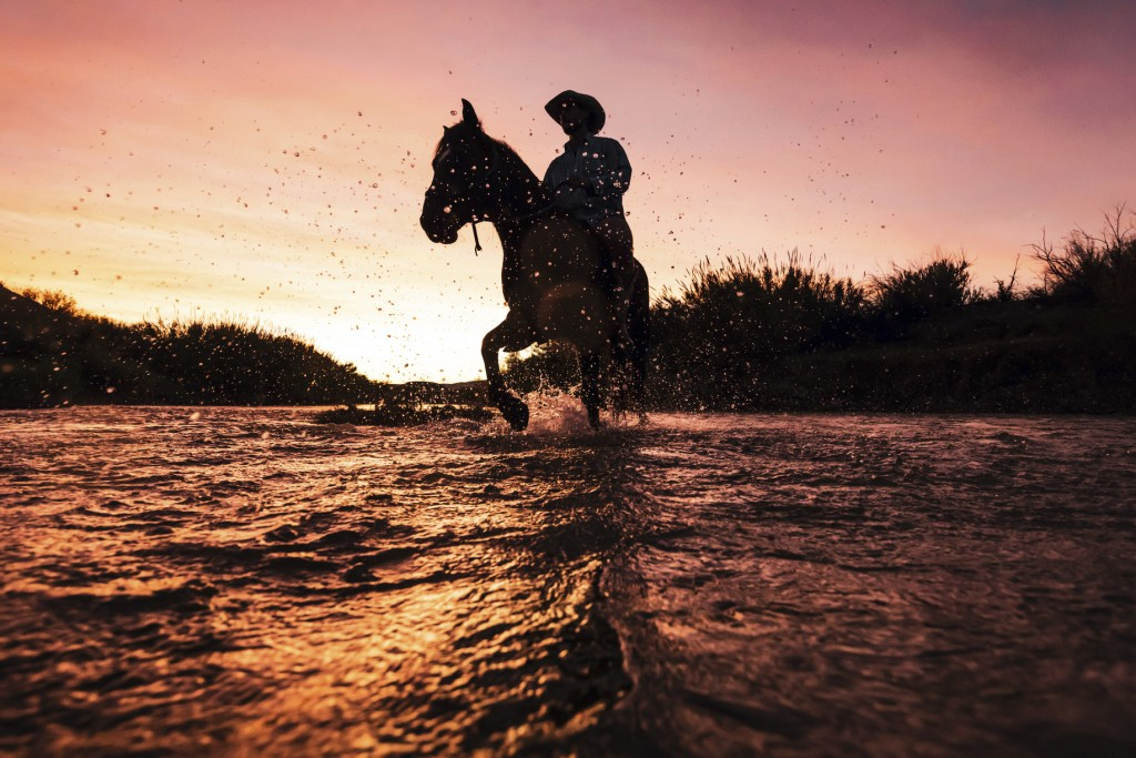 In this December, 2017 photo released by Fin and Fur Films, filmmaker Ben Masters rides horseback in the Rio Grande along the U.S.-Mexico border in Bi...