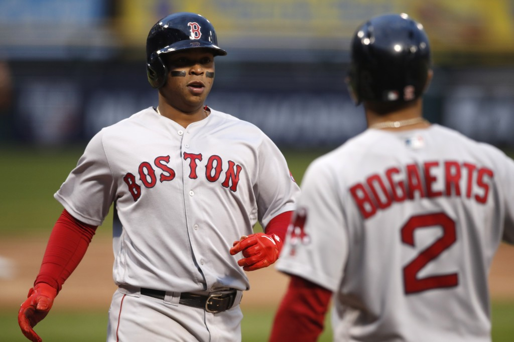 Boston Red Sox's Rafael Devers, left, is greeted by teammate Xander Bogaerts after hitting a three-run home run off Chicago White Sox starting pitcher...
