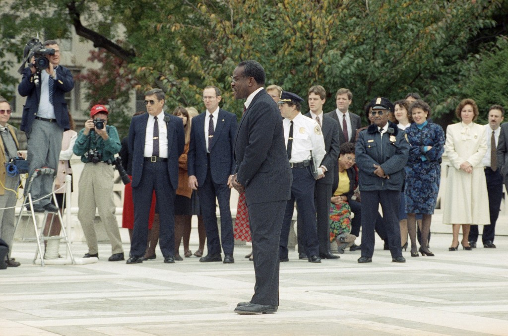FILE - In this Nov. 1, 1991, file photo, newly sworn-in Supreme Court Justice Clarence Thomas talks to reporters while posing on the plaza of the cour...