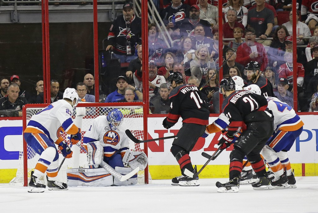 Carolina Hurricanes' Justin Williams (14) scores against New York Islanders goalie Thomas Greiss (1), of Germany, during the second period of Game 4 o...