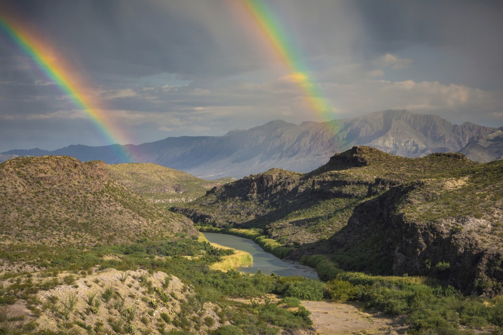 This December, 2017 photo released by Fin and Fur Films shows a double rainbow over Big Bend National Park, Texas, and the Rio Grande along the U.S.-M...