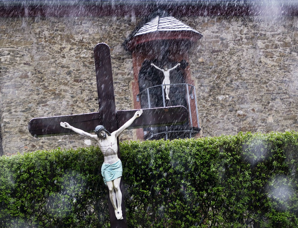 Snow falls on two Jesus crosses in front of a church in Seelenberg near Frankfurt, Germany, Saturday, May 4, 2019. (AP Photo/Michael Probst)