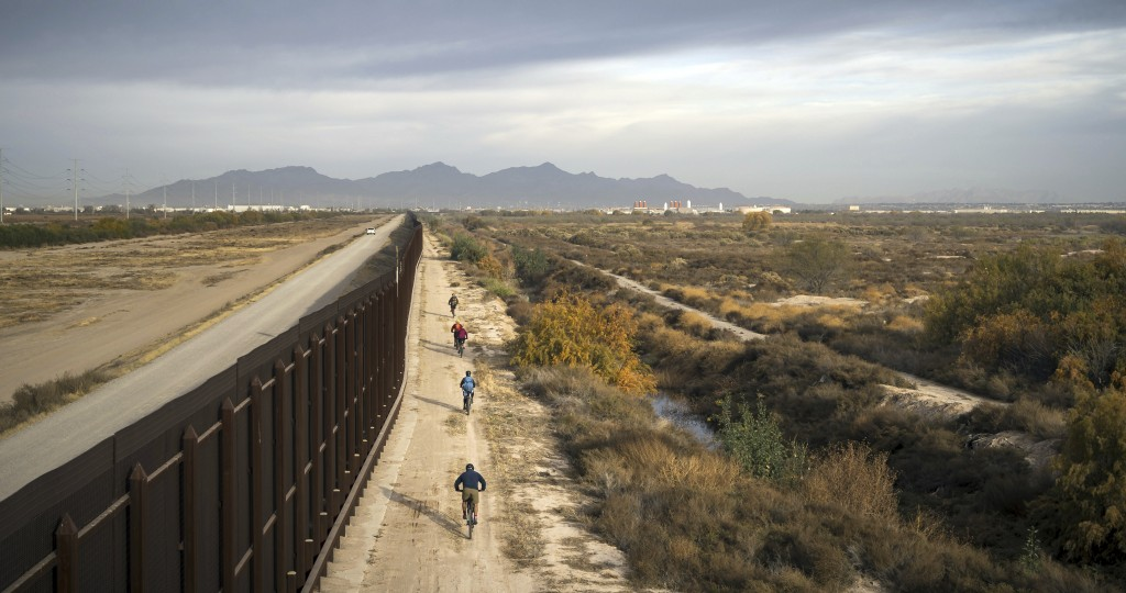 In this January, 2018 photo released by Fin and Fur Films, a group of filmmakers and wildlife photographers cycle along the border wall near the U.S.-...