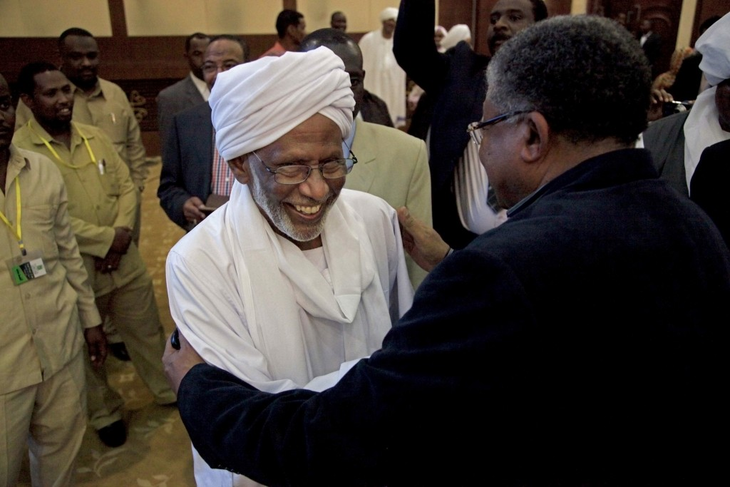 FILE - In this Jan. 27, 2014 file photo, Sudanese religious and Islamist political leader Dr. Hassan al-Turabi, center, is greeted as he attends a spe...