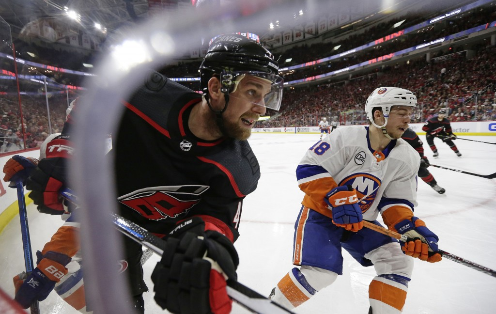 Carolina Hurricanes' Calvin de Haan, left, and New York Islanders' Anthony Beauvillier (18) chase the puck during the second period of Game 4 of an NH...
