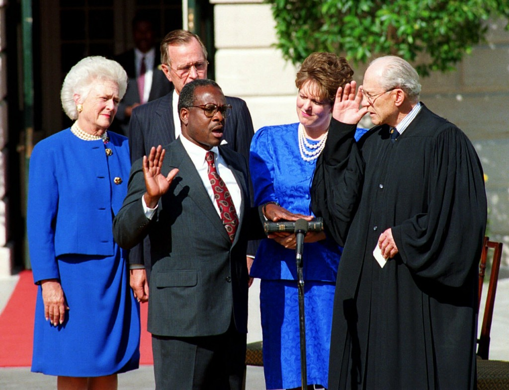 FILE - In this Oct. 18, 1991, file photo, Clarence Thomas is sworn in to the Supreme Court in Washington, by Justice Byron White. Watch from left are ...