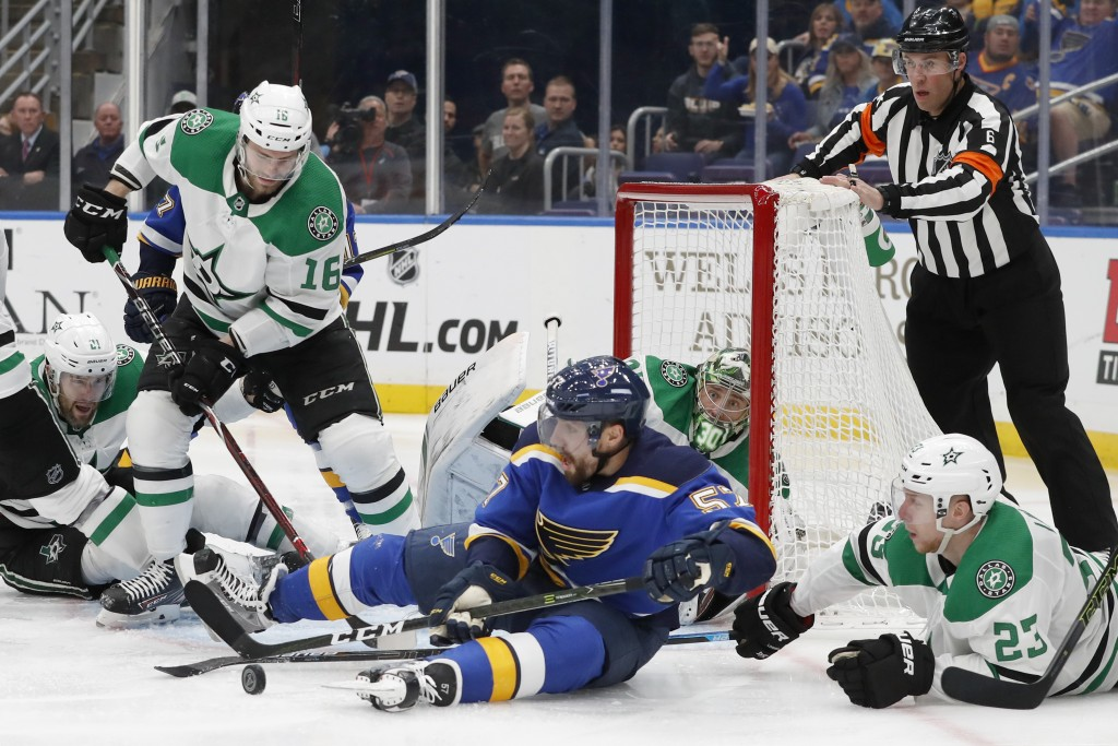 St. Louis Blues left wing David Perron (57) reaches for the puck after falling to the ice with Dallas Stars defenseman Esa Lindell (23), of Finland, d