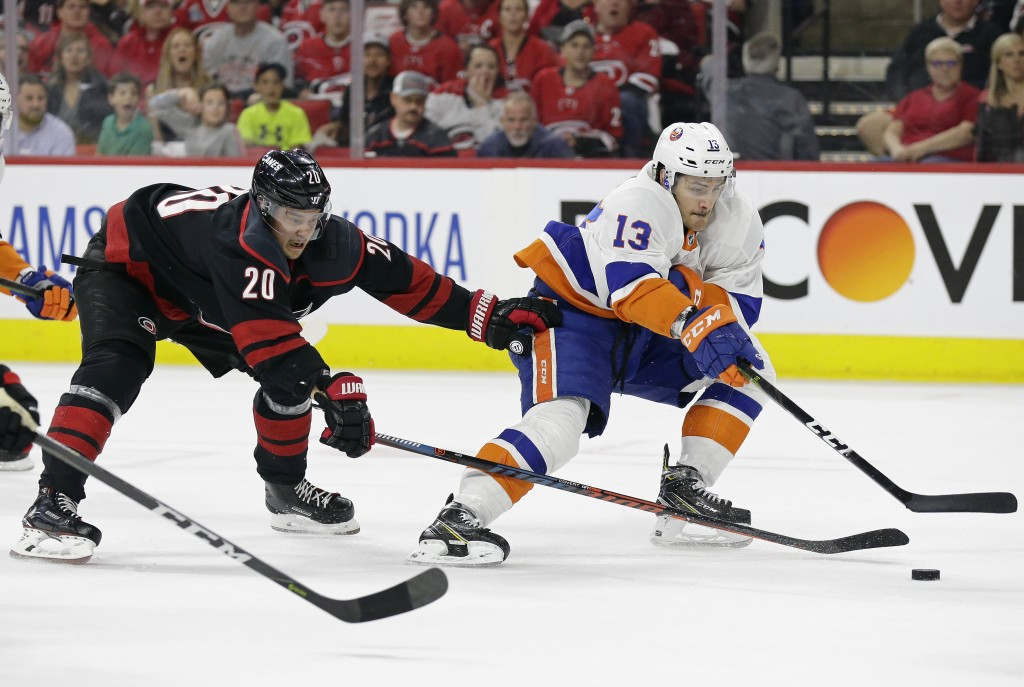 Carolina Hurricanes' Sebastian Aho (20), of Finland, chases New York Islanders' Mathew Barzal (13) during the first period of Game 4 of an NHL hockey