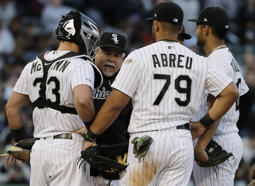 Chicago White Sox manager Rick Renteria, second from left, talks with his team during the third inning of a baseball game against the Boston Red Sox i