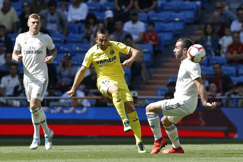 Villarreal's Santi Cazorla, centre, kicks the ball past Real Madrid's Dani Carvajal, right, during a Spanish La Liga soccer match between Real Madrid