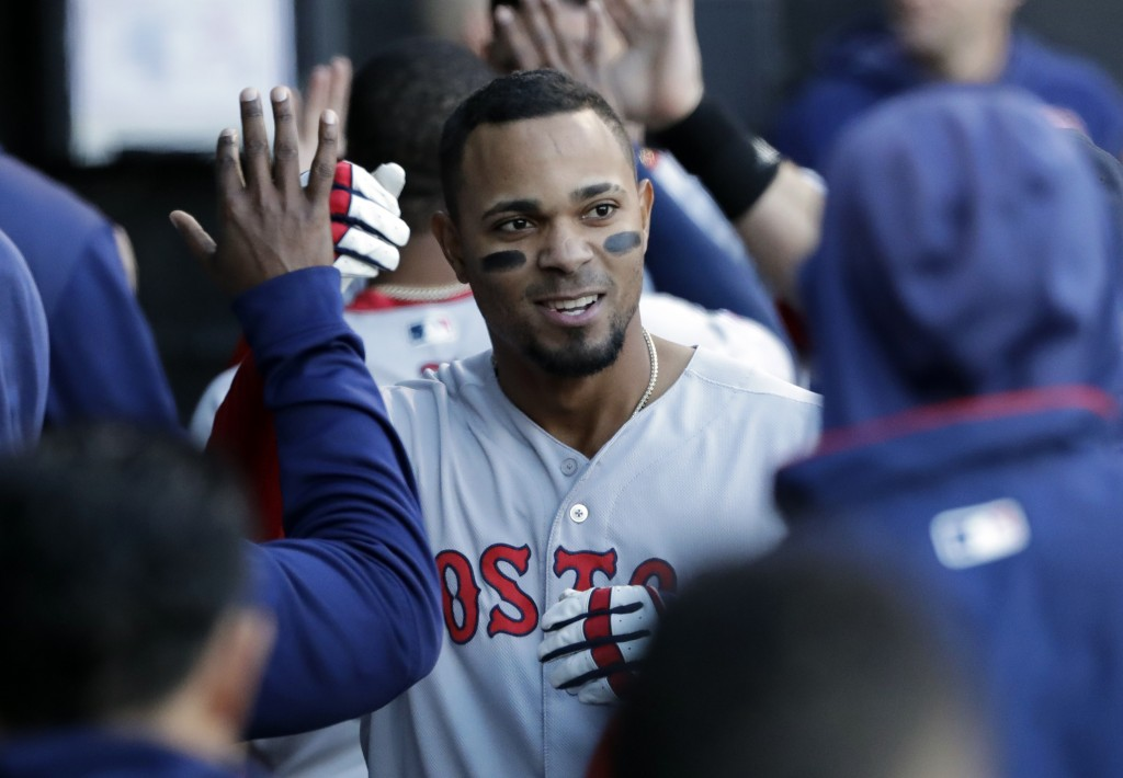 Boston Red Sox's Xander Bogaerts celebrates with teammates in the dugout after hitting a two-run home run against the Chicago White Sox during the thi...