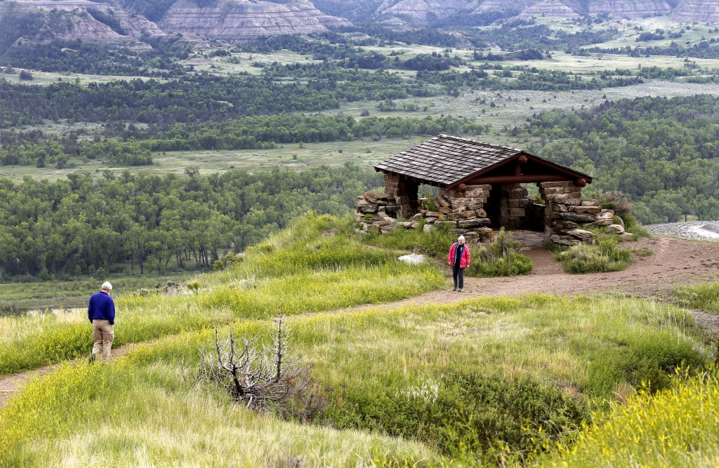 FILE - In this June 11, 2014 file photo, James Lyons and Florence Reaves, from Kirkwood, Mo., hike to a stone lookout over the Little Missouri River i...