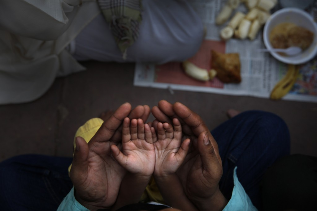 FILE - In this June 30, 2014 file photo, an Indian Muslim father holds the hands of his daughter in his palms and prays before breaking fast on the fi