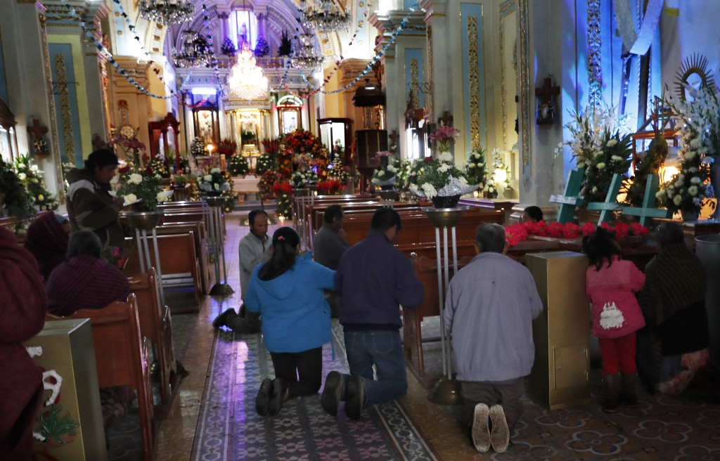 In this Thursday, May 2, 2019 photo, residents kneel in prayer marking the Day of the Holy Cross celebrations, mixing Catholic traditions with pre-His...