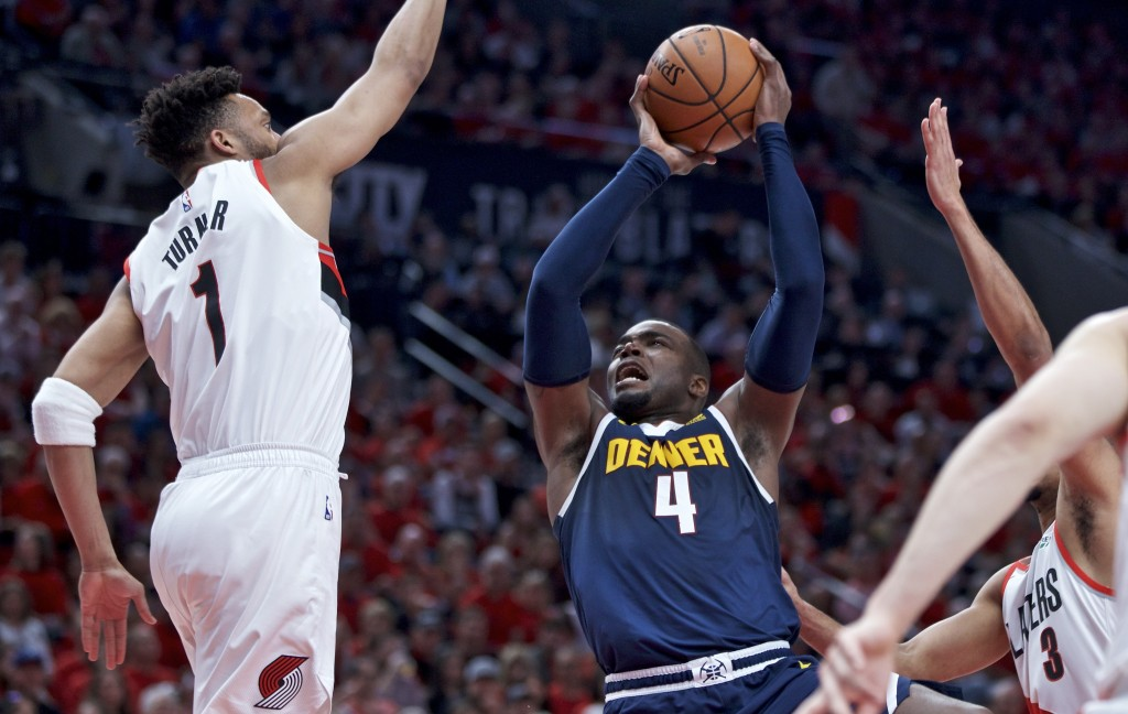 Denver Nuggets forward Paul Millsap, right, looks to shoot over Portland Trail Blazers guard Evan Turner during the first half of Game 4 of an NBA bas...