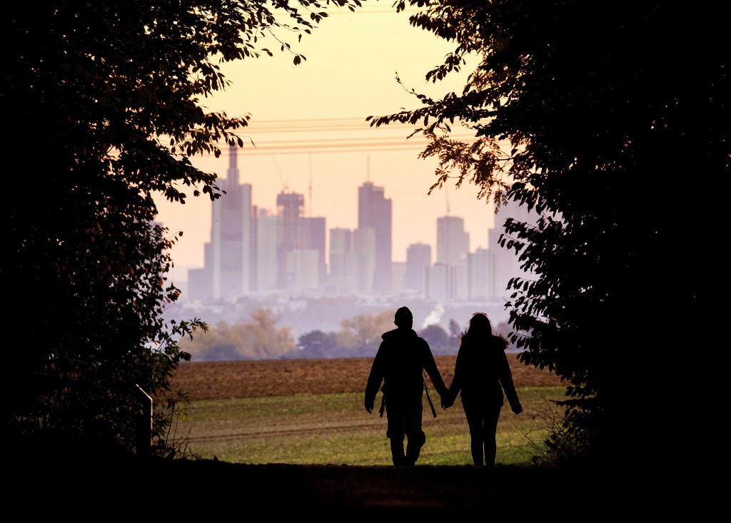 FILE - In this Oct. 21, 2018, file photo, a couple walks through a forest with the Frankfurt skyline in background near Frankfurt, Germany. Developmen
