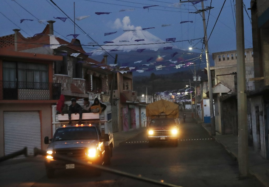 In this Friday, May 3, 2019 photo, drive through the streets in village Santiago Xalitzintla, Mexico as the Popocatepetl volcano spews ash nearby. The...