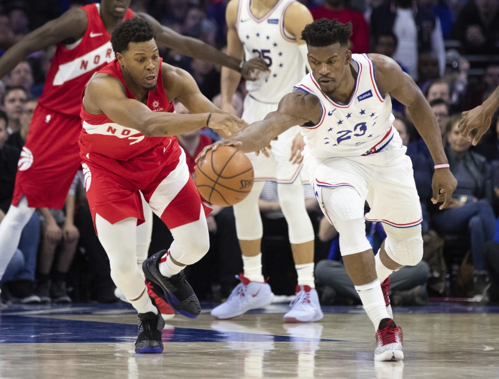 Toronto Raptors' Kyle Lowry, left, and Philadelphia 76ers' Jimmy Butler, right, go after a loose ball during the second half of Game 4 of a second-rou...