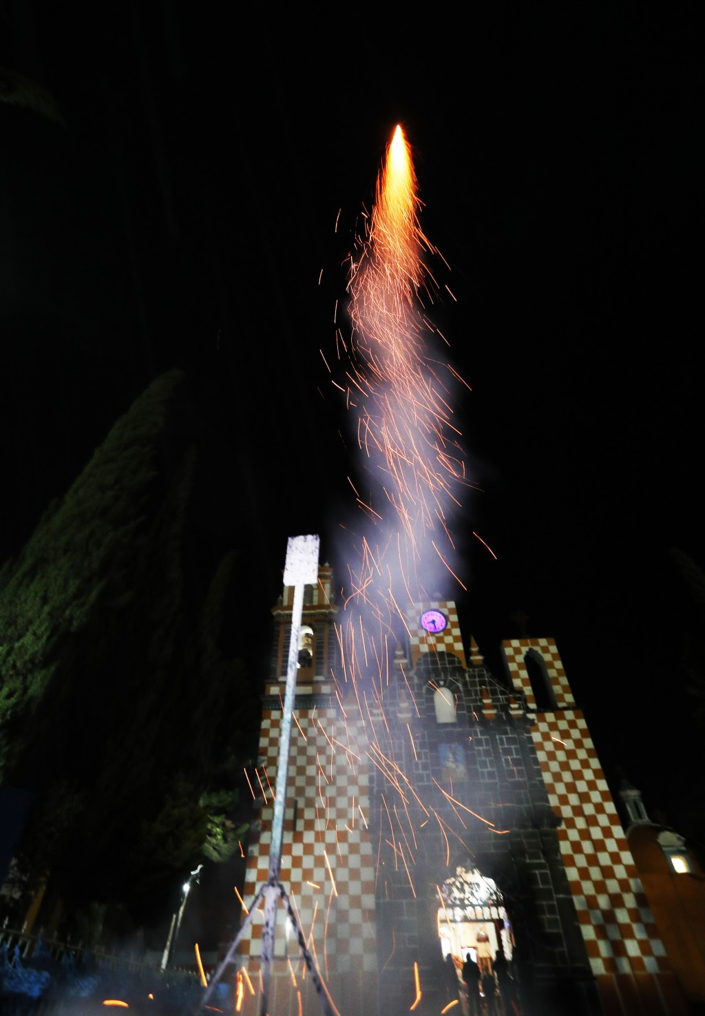 In this Thursday, May 2, 2019 photo, a fireworks shoots past during celebrations marking the Day of the Holy Cross that mixes Catholic traditions with...