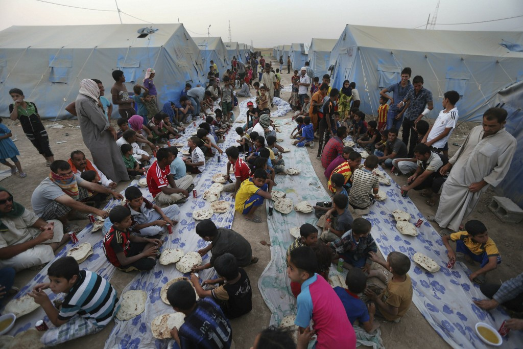 FILE - In this June 29, 2014 file photo, displaced Iraqi citizens gather for a communal meal to break their fast during the first day of the Islamic h...