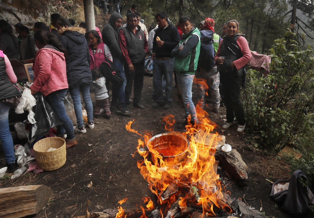 In this Friday, May 3, 2019 photo, celebrants stand near open fires cooking communal meals, on the flanks of the Iztaccíhuatl volcano or The Sleeping ...