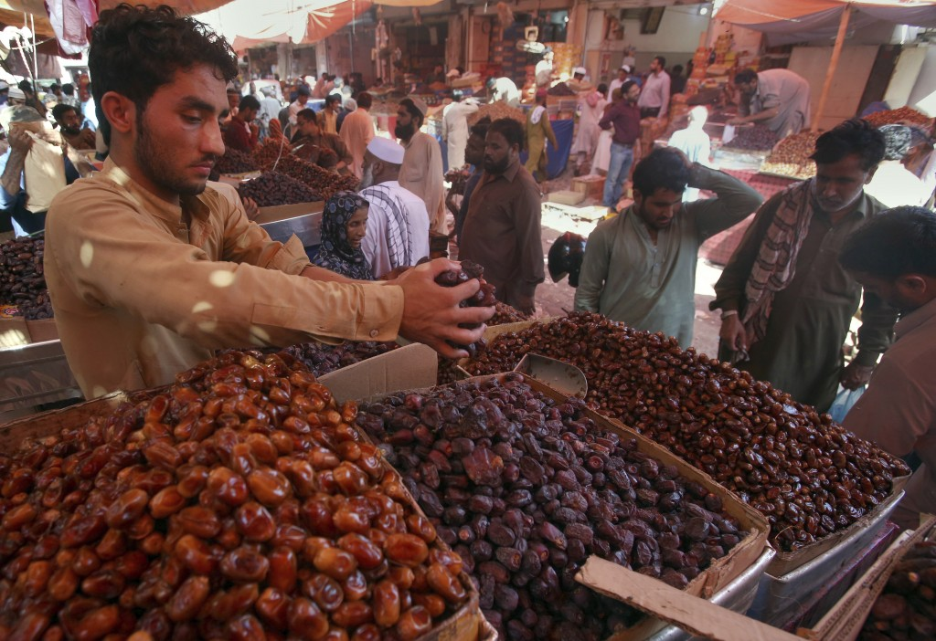 FILE - In this Sunday, May 5, 2019 file photo, people buy dates, a favorite food for Muslims' fasting month of Ramadan, at a wholesale market in Karac...