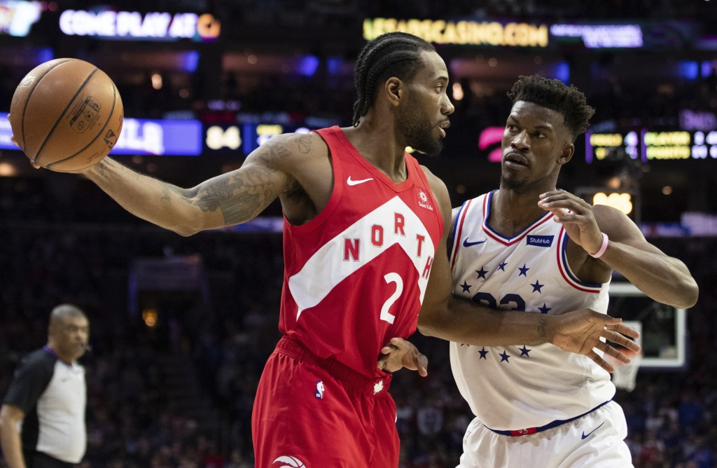 Toronto Raptors' Kawhi Leonard, left, holds the ball away from Philadelphia 76ers' Jimmy Butler, right, during the second half of Game 4 of a second-r...