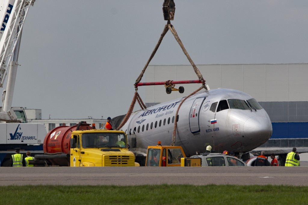 A crane lifts the damaged Sukhoi SSJ100 aircraft of Aeroflot Airlines in Sheremetyevo airport, outside Moscow, Russia, Monday, May 6, 2019. Russian em