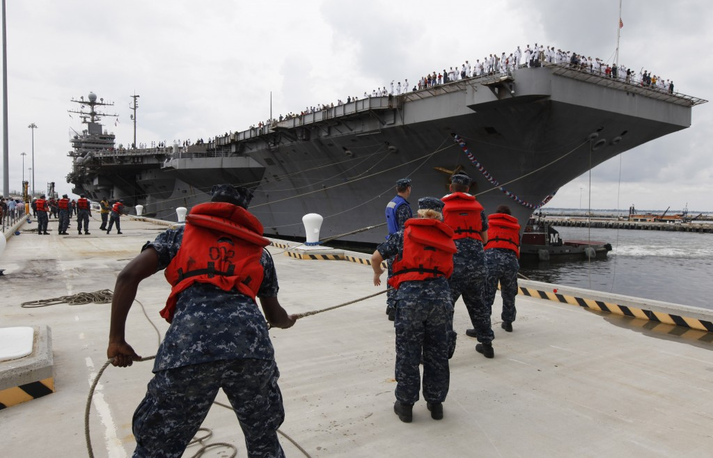 FILE - In this Aug. 7, 2012, file photo, Navy shore crew haul in lines as the nuclear powered aircraft carrier USS Abraham Lincoln arrives at Naval St...