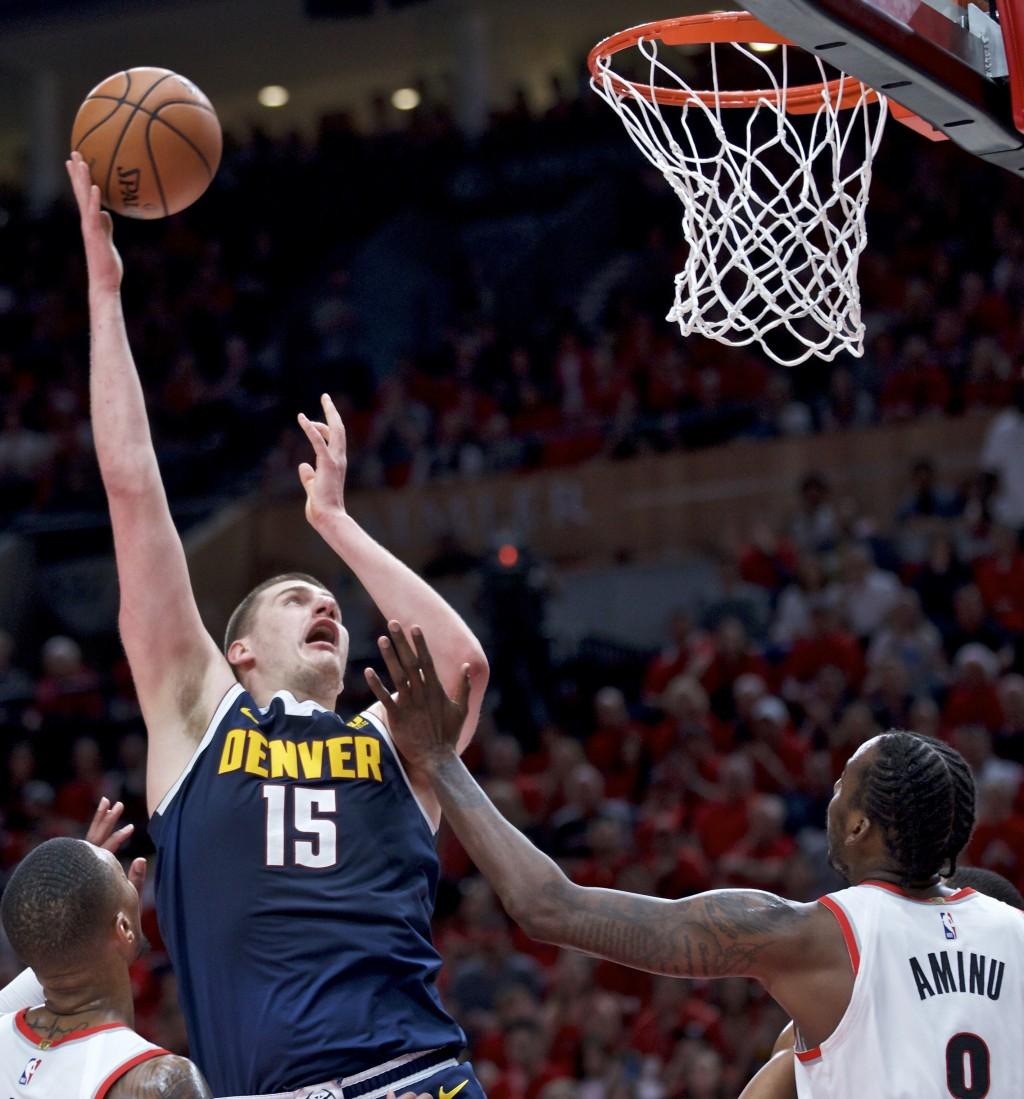 Denver Nuggets center Nikola Jokic, left, shoots over Portland Trail Blazers forward Al-Farouq Aminu during the first half of Game 4 of an NBA basketb...