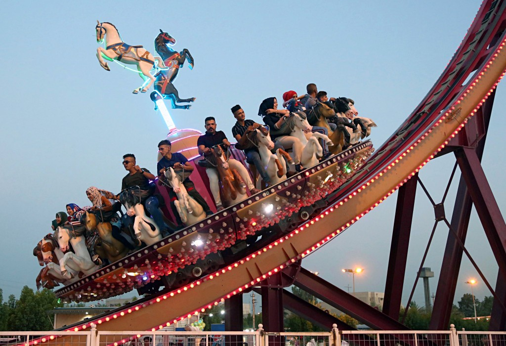 FILE - In this June 16, 2018 file photo, people take a ride at an amusement park during Eid al-Fitr celebrations, that mark the end of the Muslim holy...