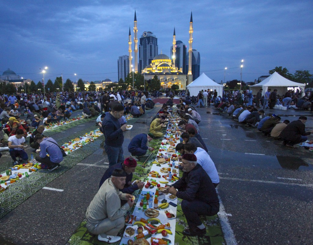 FILE - In this July 11, 2018 file photo, Chechens wait to break their fast at a roadside during the Muslim fasting month of Ramadan, at the main Mosqu...