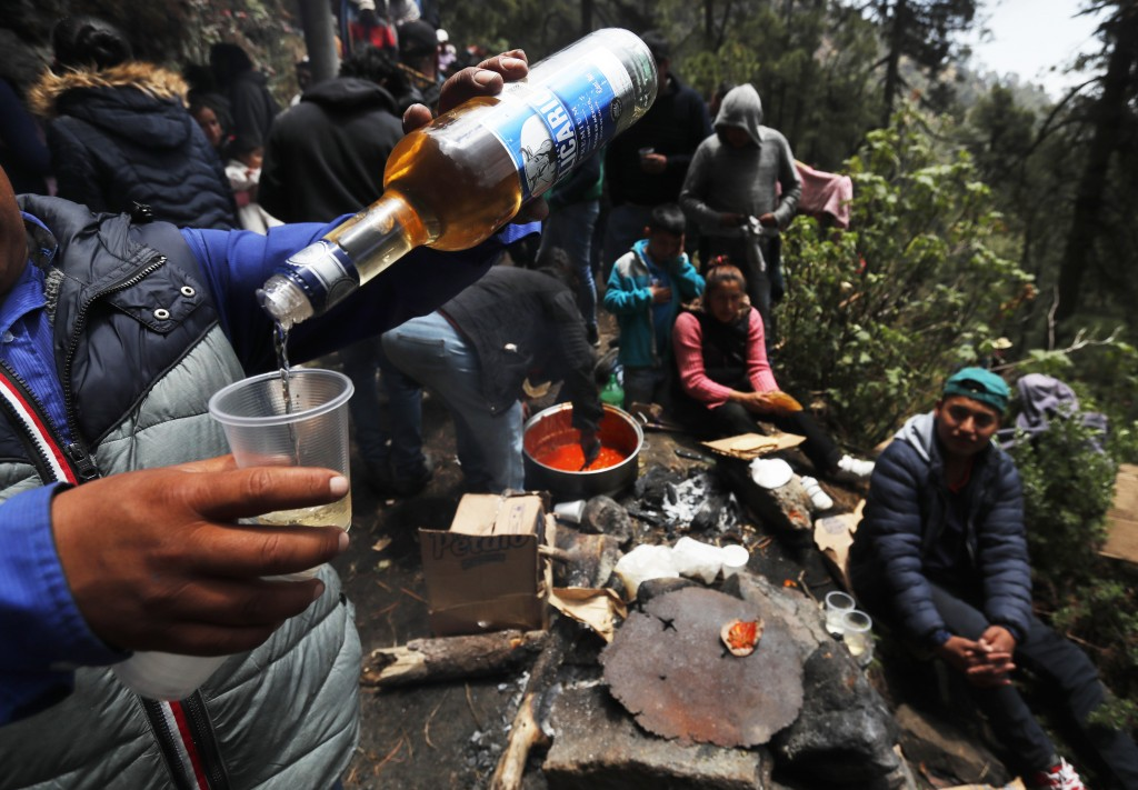 In this Friday, May 3, 2019 photo, a celebrant pours liquor into a plastic cup on the flanks of the Iztaccíhuatl volcano or The Sleeping Woman (the vo...