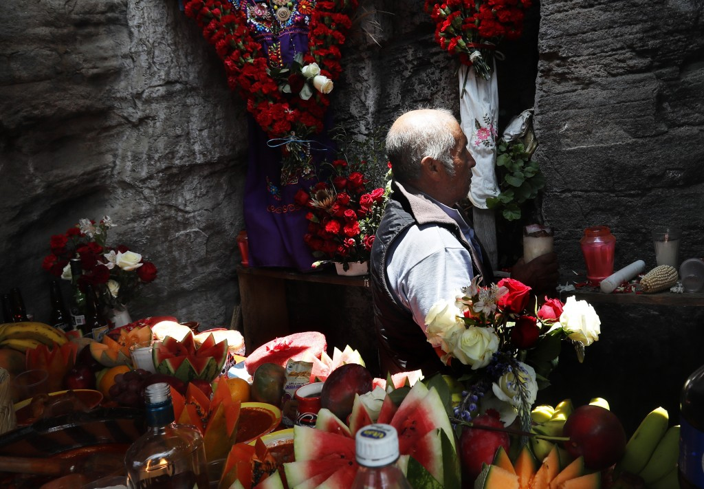 In this Friday, May 3, 2019 photo, Nasario Galicia tends to the altar, tucked inside a nook in the stone walls of on the base of the Iztaccíhuatl volc...