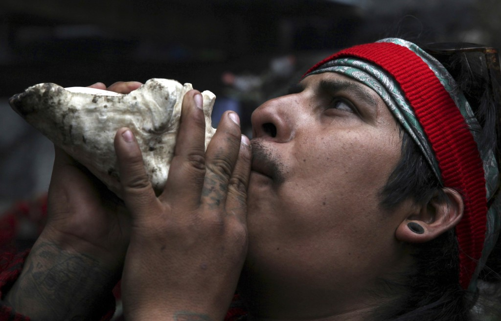 In this Friday, May 3, 2019 photo, a resident blows on a conch shell to honor Tonantzin, the Aztec mother earth goddess that's often celebrated alongs...