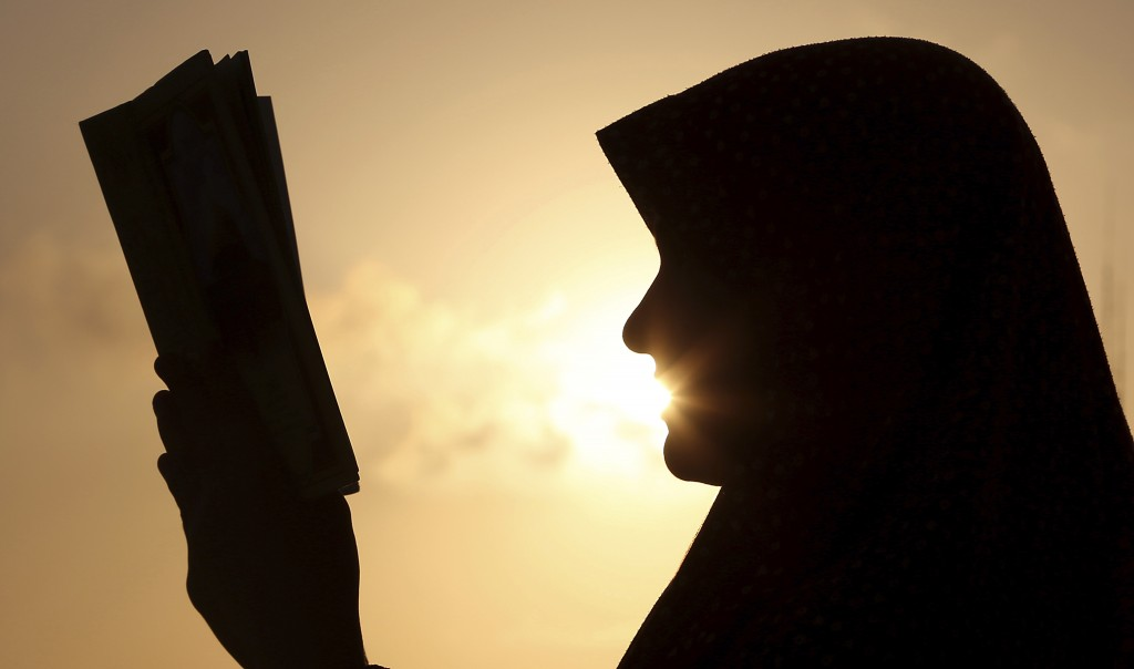 FILE - In this July 4, 2014 file photo, a Palestinian girl reads the Quran, Islam's holy book during Ramadan, at sunset in Gaza City. Most Muslims aro...
