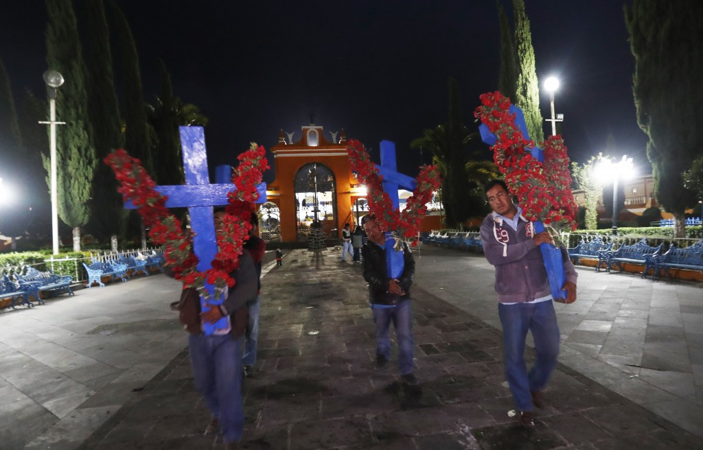 In this Thursday, May 2, 2019 photo, pilgrims arrive with crosses adorned with red flowers marking the Day of the Holy Cross celebrations, mixing Cath...