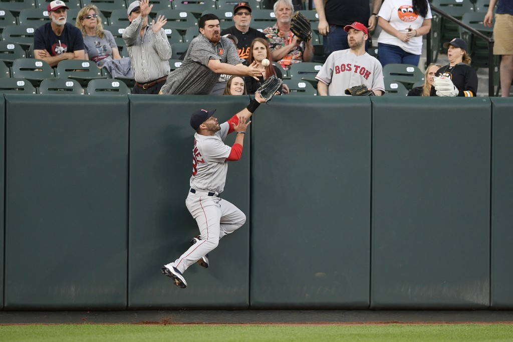 Boston Red Sox left fielder J.D. Martinez (28) and a fan reach for a ball hit by Baltimore Orioles' Jonathan Villar during the first inning of a baseb...