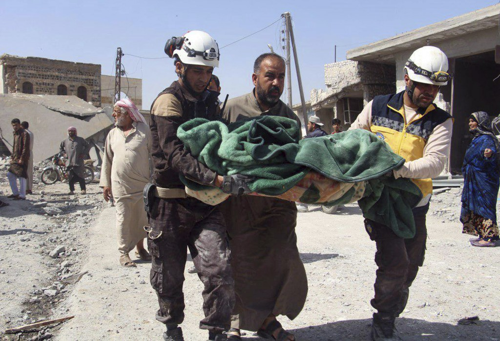This photo provided by the Syrian Civil Defense group known as the White Helmets, shows members of the Syrian Civil Defense workers carrying a victim