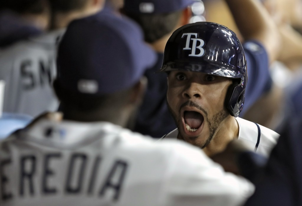 Tampa Bay Rays' Tommy Pham, right, celebrates in the dugout with Guillermo Heredia after hitting a grand slam off Arizona Diamondbacks starting pitche...