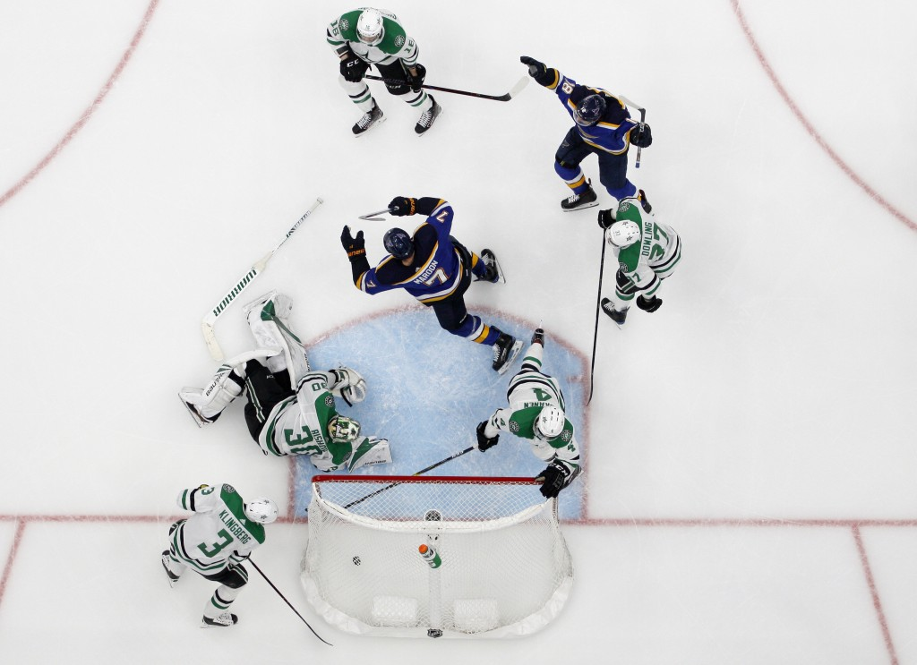 St. Louis Blues' Pat Maroon (7) and Robert Thomas (18) celebrate a score by Maroon, as Dallas Stars' John Klingberg (3), Ben Bishop (30), Miro Heiskan...