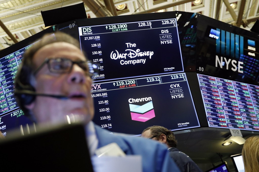 FILE - In this April 12, 2019, file photo the logos for The Walt Disney Company and Chevron appear above a trading post on the floor of the New York S