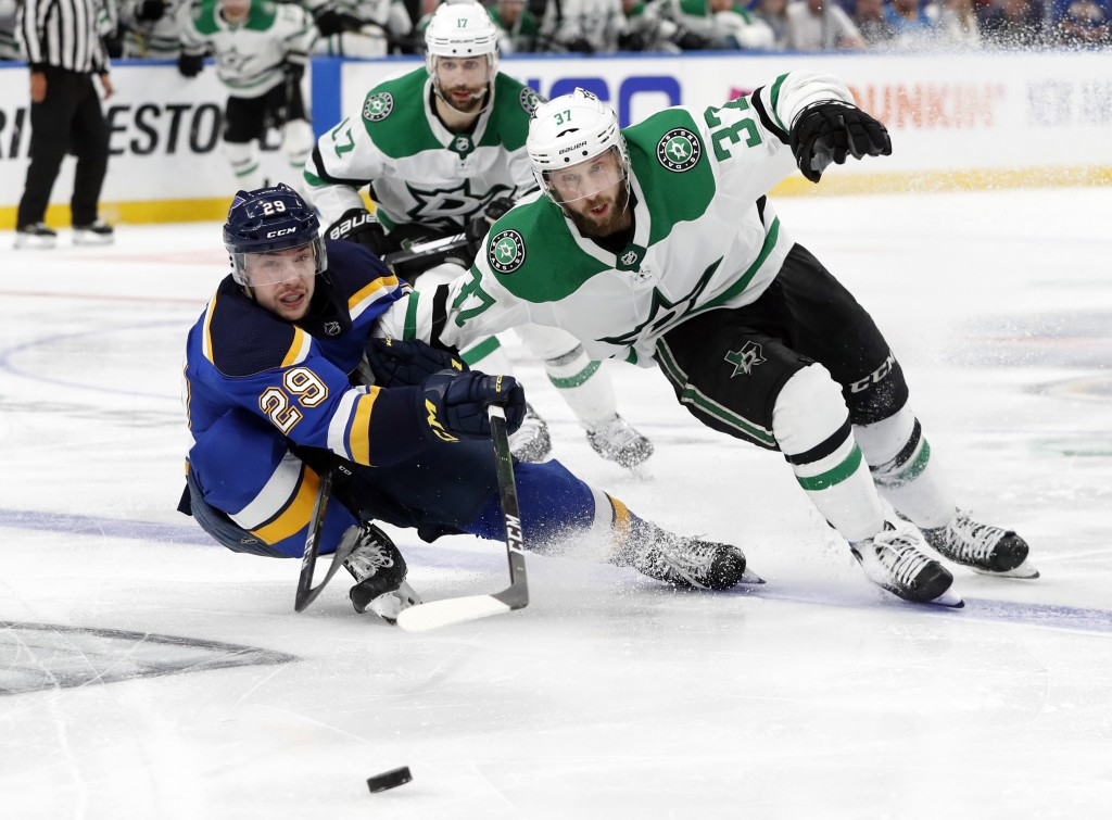 St. Louis Blues' Vince Dunn (29) and Dallas Stars' Justin Dowling (37) move to control the puck as Andrew Cogliano, rear, looks on during the second o