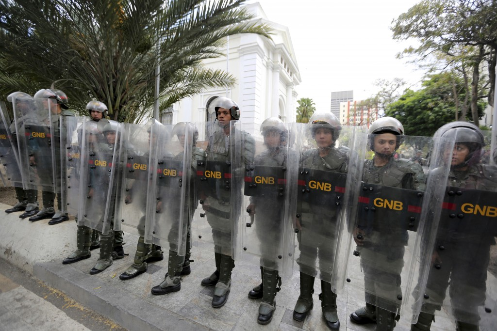 Venezuelan Bolivarian National guards officers form a cordon around the National Assembly building as the opposition-controlled congress met to discus...