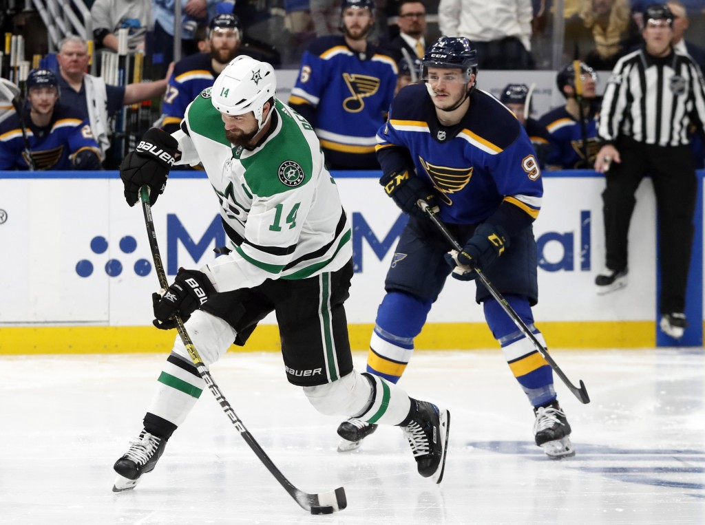 Dallas Stars' Jamie Benn (14) shoots the puck as St. Louis Blues' Sammy Blais (9) looks on during the second overtime period in Game 7 of an NHL secon...